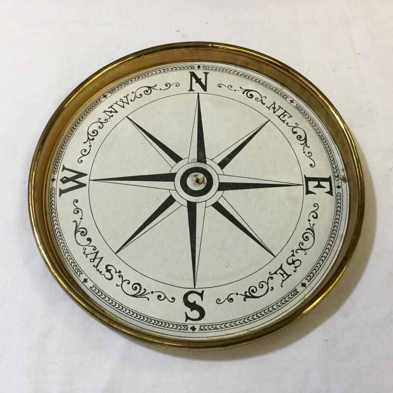 Paper compass rose in brass surround